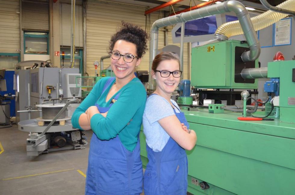 Zwei Frauen stehen Rücken an Rücken in einer Werkshalle