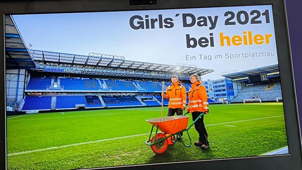 Zwei Mädchen mit Schubkarre auf einem Sportplatz