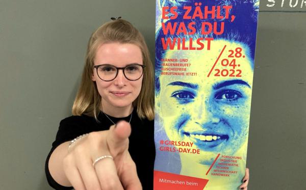 Junge Frau mit Plakat zeigt in die Kamera
