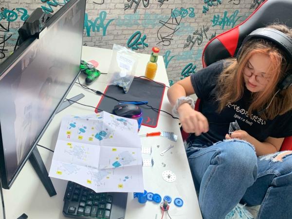 Mädchen am Computer mit Konstruktionsteilen