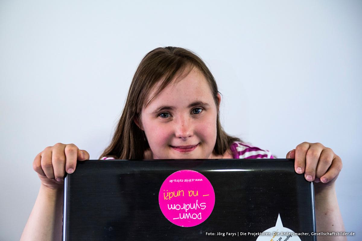 Mädchen hinter einem geöffnetem Laptop