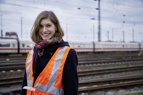 Frau mit Warnweste vor einem Zug