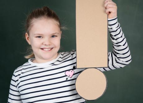 Ein Mädchen hält ein großes Ausrufezeichen in der Hand