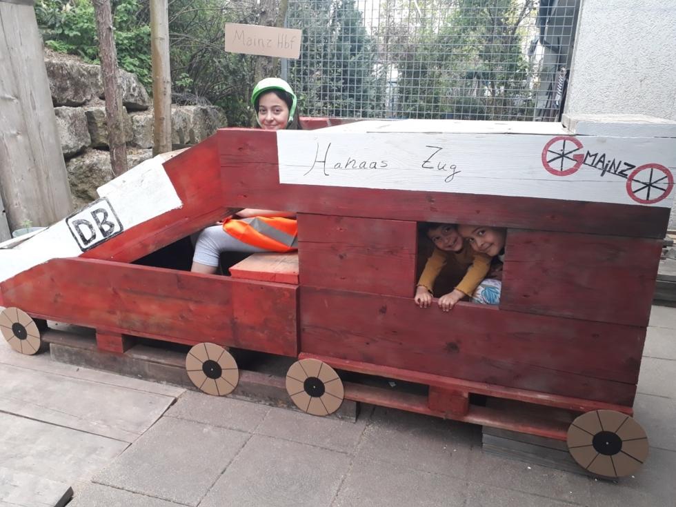 Mädchen mit Helm in einem selbstgebauten Holzzug