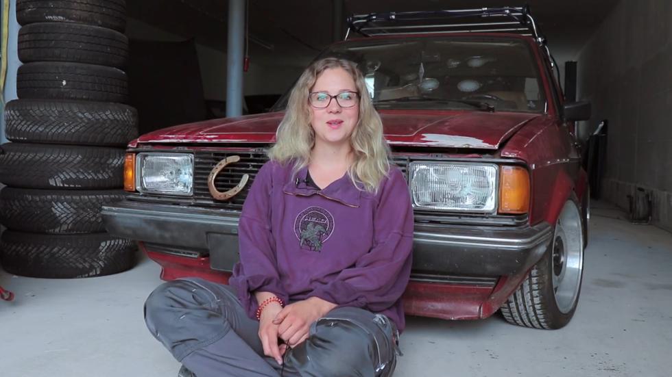 Junge Frau sitzt vor einem Auto