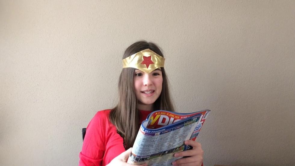 Mädchen mit Stirnband liest eine Zeitschrift