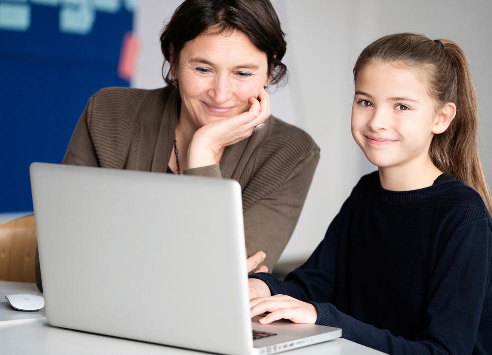 Eine Frau und ein Mädchen sitzen vor einem Laptop