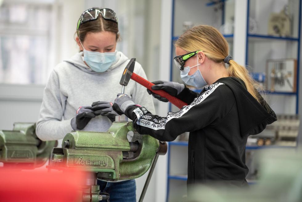 Zwei Mädchen mit Maske arbeiten am Schraubstock