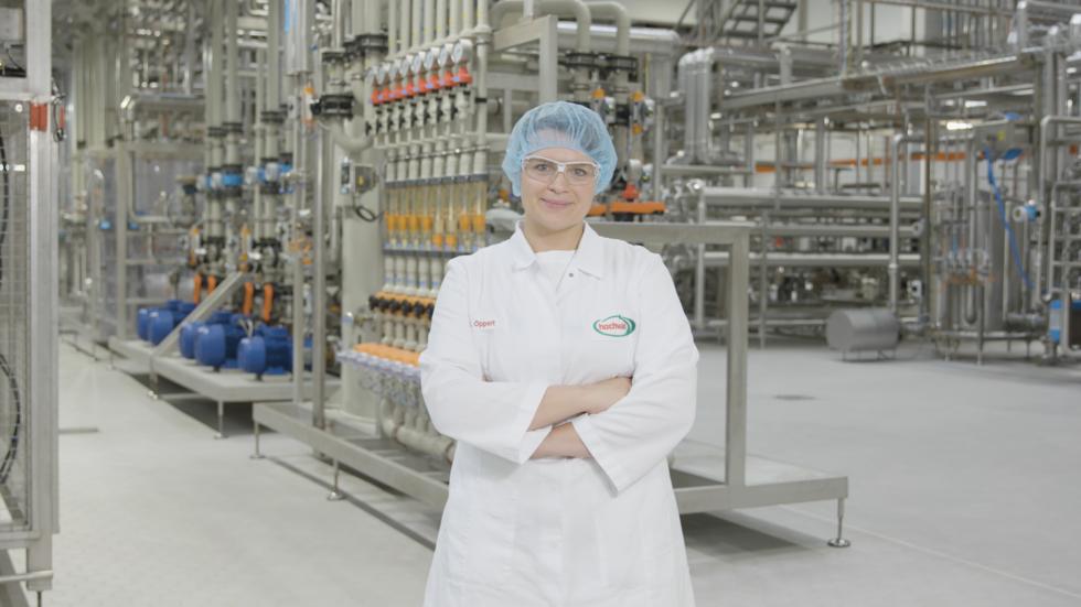 Frau in Laborkleidung in einer Werkshalle