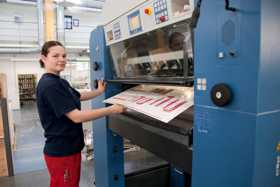 Junge Frau steht vor einer Druckmaschine